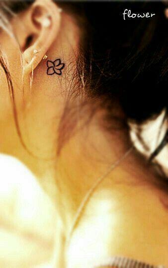 Piccolo fiore dietro l'orecchio tattoo.