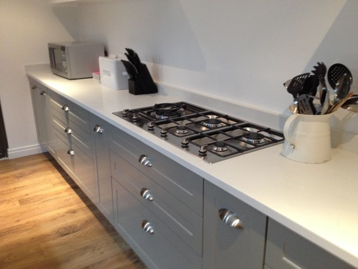 My new modern kitchen...white stone tops and gray no slam cupboards with a Smeg gas hob