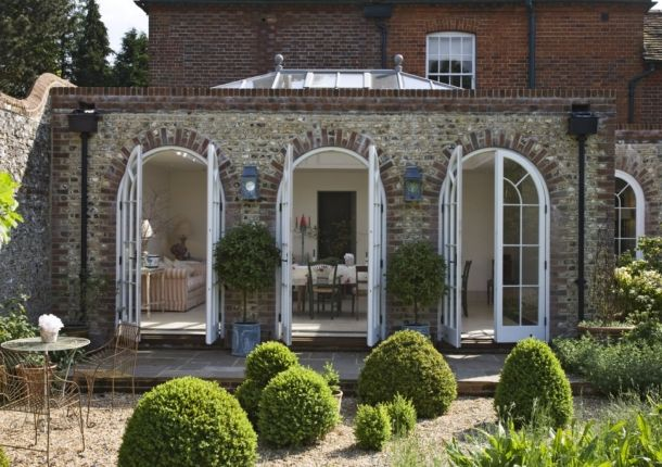A traditional orangery with brick and flint walls, arched doors and glazed lantern roof
