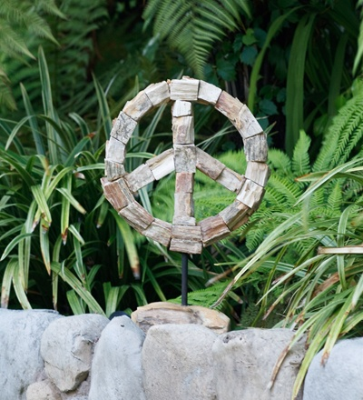 Petrified Wood Peace Symbol on a garden stake! The Peace Sign first appeared in 1958 at a Nuclear Disarmament March in London. Designed by Gerald Holtom for use as a Nuclear Disarmament logo, it combines the semaphore signals for the letter N (two flags held in an upside-down V shape) and D (one straight up and the other straight down). Never patented, the symbol was adopted by the peace movement, and is today an internationally recognized sign of peace. Groovy!