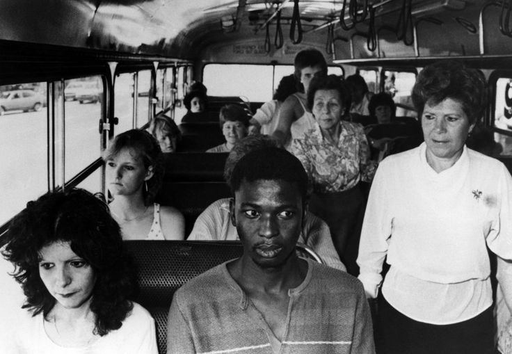 A young black man, in an act of resistance to South Africa's apartheid policies, riding a bus restricted to whites only, in Durban. 1986