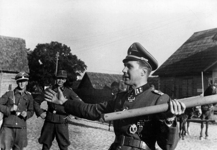 """Estonian SS-Obersturmbannführer  Harald Reibach explains to other SS officers the proper procedure for using a Panzerfaust rocket launcher. Riipalu was decorated with the Knight's Cross on 23 August 1944 for successfully leading the Waffen-Grenadier Regiment der SS 45 of the Estonian 20. Waffen Grenadier Division der SS in the Battle of Tannenberg """". This photo was taken in the autumn of 1944."""