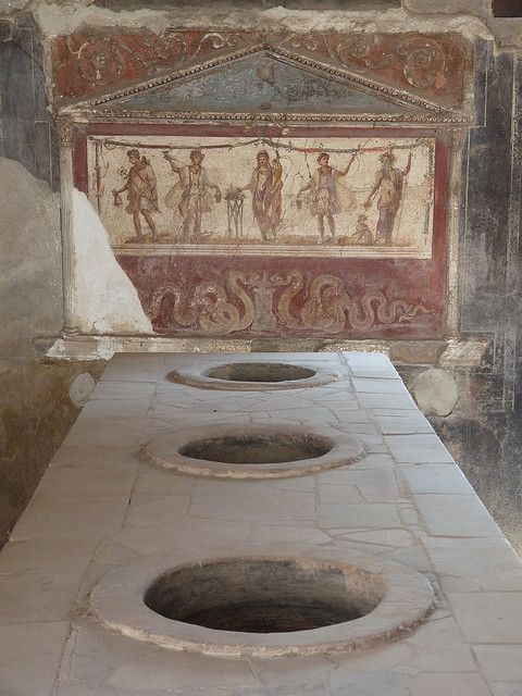 thermopolium in pompeii. thermopolium is a kind of roman bar which served hot and cold drinks. the tiled bar-top is fitted with recessed terracotta jars that would have contained the drinks. on the back wall is a fresco painting: specifically it is a lararium (a shrine to roman household gods), featuring bacchus on the far right and mercury on the far left. this particular example is called the thermopolium of vetutius placidus and is located on the via dell'abbondanza in pompeii.