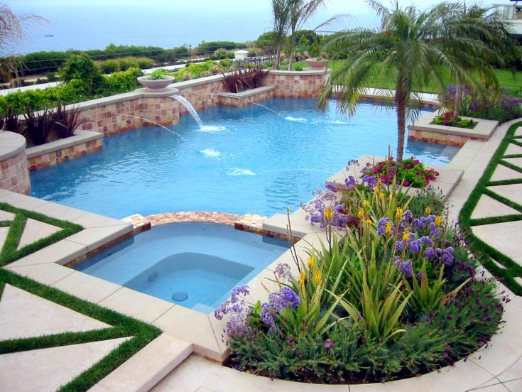 A tile wall runs the length of this crystal-blue swimming pool adding color and including multiple fountains and planters. A built-in hot tub sits to the side of the pool next to a beautifully landscaped patio space with grass growing in a geometric design. A thriving area of flowers, palm trees and ornamental grasses lines the pool with bountiful color.