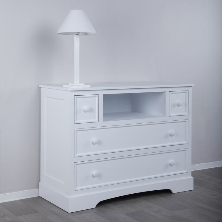 White wooden chest of drawer and white lamp
