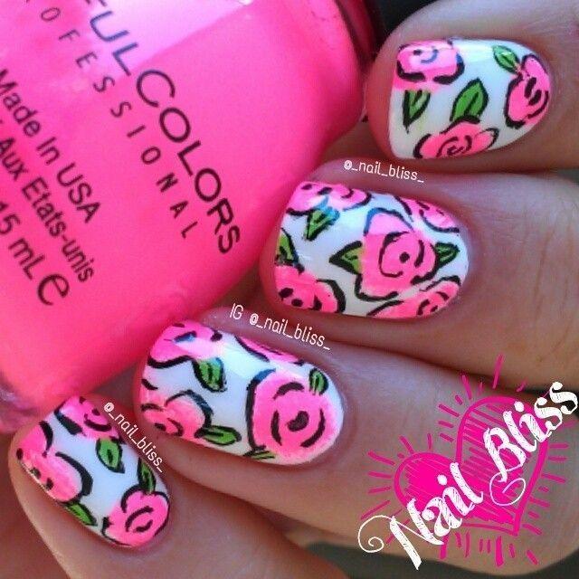 Bellas uñas en color blanco, decoradas con diseños de flores en rosa neon, bordes negros y hojas verdes.
