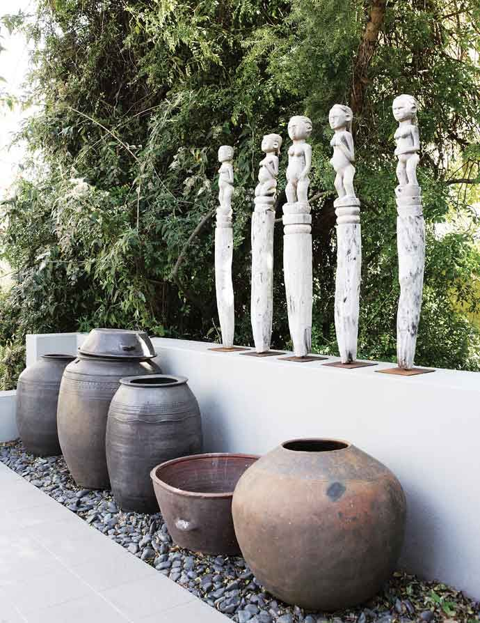 A series of hand-crafted totems above Korean Kimchi pots.