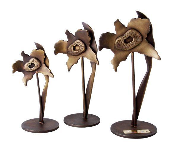 Peça: bidimensional com relevos, disponível em 3 tamanhos:  19,5 ; 23,5 e 27,5 cm de altura.  Materiais disponíveis: bronze (dourado ou patinado).  Placa cortesia: latão (dourada), 4x1,5cm.