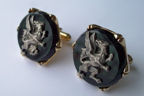 4497 c. 1960s Shield's striking griffin cufflinks in high relief against black background. Griffin looks to be pewter like material. Hexagonal pronged setting. Large- over an inch in diameter. Price: $30