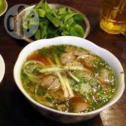 Pho (Sopa vietnamita de carne com macarrão) @ allrecipes.com.br - O caldo quente da sopa é colocado sobre as finas fatias de carne, cozinhando a carne. Em seguida, acrescenta-se manjericão, coentro, broto de feijão e pedaços de limão.