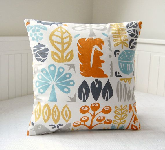 This lovely 16 inch decorative pillow cover has an orange squirrel and leaves and trees in shades of teal aqua, light mustard yellow and orange