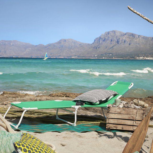 Un bain de soleil IKEA tout vert installé sur les rochers en bord de mer avec un coussin noir et blanc