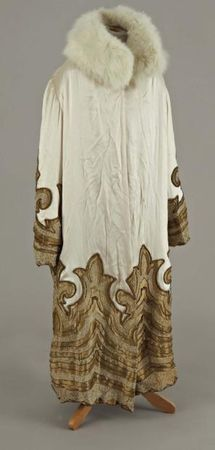Paul Poiret, 1925.  ivory satin, white fox collar, decorated with jewels, under gold lamé, Cornely embroidered lace, gold thread and gold beads, gold lame lining (slight wear to the lining at the shoulder)