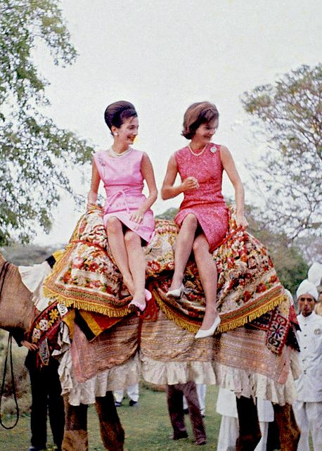 Lee Radziwill and Jackie Kennedy wearing pink Oleg Cassini dresses on top of a camel during their tour of Pakistan in 1962.