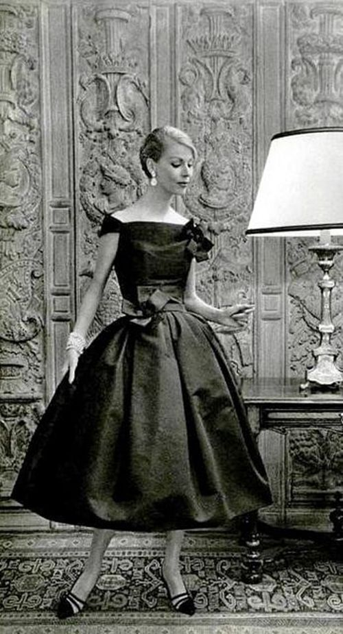 """Italian socialite Felicidade de Sousa Campos, posing before a sculpted wall, wears a creation of Christian Dior in 1957. Dior's Spring 1955's """"A-line"""" collection had dresses with a less defined and narrower waist and a smooth silhouette that widened over the hips and legs, which resembled a capital """"A."""""""