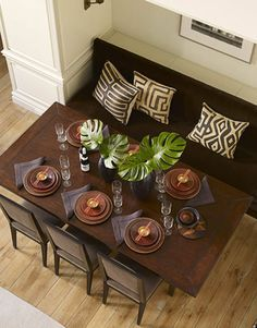 """The owners wanted the living room to be a """"multipurpose room,"""" so Maya created a dining area with a built-in banquette. The three chairs do double duty at a nearby game table."""
