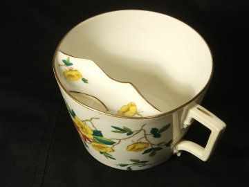 This is a moustache cup.  It was used in the Victorian times, if you had a particularly large moustache, you would rest the moustache on the little ledge bit inside the cup, and drink through the hole, to avoid getting your moustache wet.