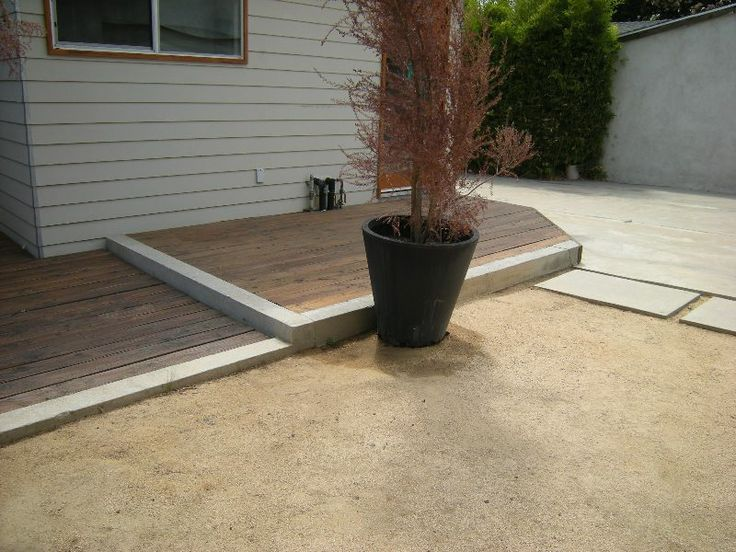 Ground-level deck in a poured concrete curb with step.