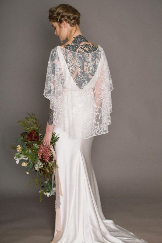 The 'Faith' dress with detachable beaded lace cape by Rolling in Roses, available to buy exclusively at www.rollinginroses.co.uk .  low V bias cut silk satin long train low back backless bridal plaits plaited hair tattooed bride made in England Britain long veil crystal crown simple wedding gown