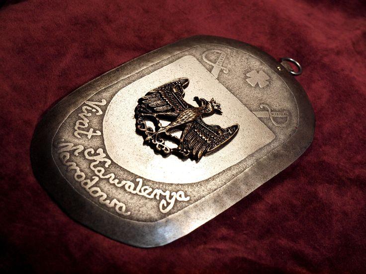 Pracownia Artystyczna LORICA. RYNGRAF, KAPLERZ, POLISH GORGET. Kaplerz patriotyczny, kawaleryjski. Na środku tarcza z mosiężnym orłem - wzór orła zaczerpnięty z grobowca króla Kazimierza Jagiellończyka autorstwa Wita Stwosza. Powyżej dwie szable, pomiędzy nimi krzyż kawalerski. Poniżej napis: VIVAT KAWALERYA NARODOWA.