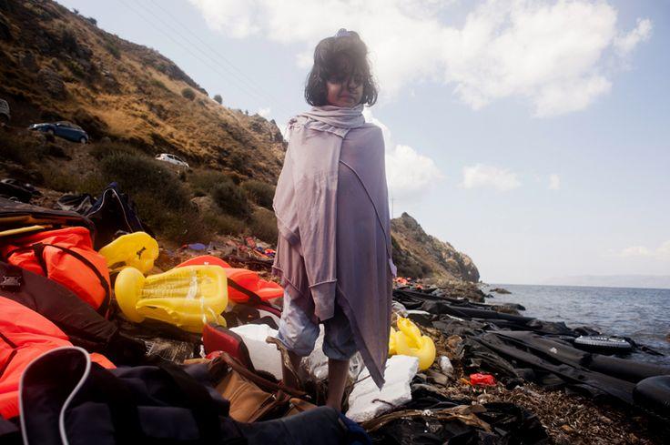 Una niña se cubre con un suéter mientras observa como los migrantes llegan en botes inflables en la isla griega de Lesbos.