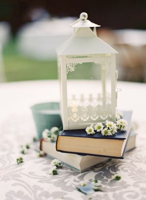 lanterns on stacked books w/ sprigs of flowers scattered around.