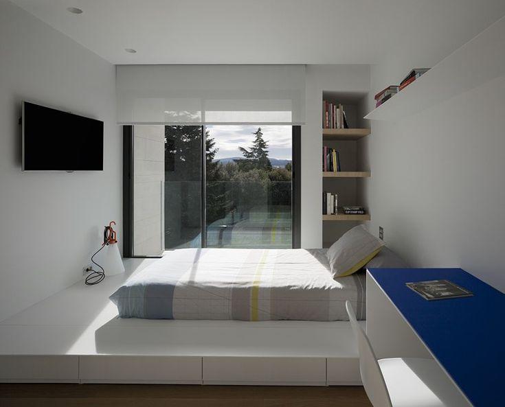 Flachbild-Fernseher an der Wand gegenüber dem Podestbett