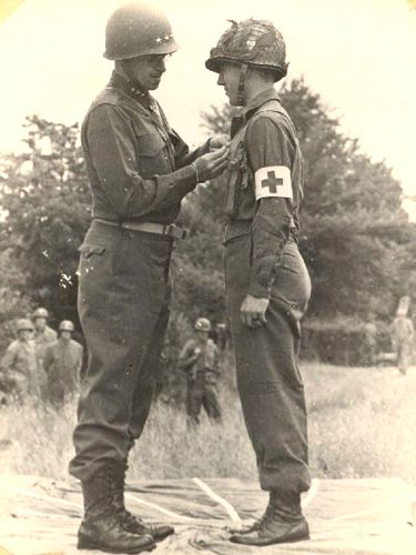 General Omar Bradley conferring the Distinguished Service Cross (DSC) on T/4 Jack Rudd (Company B) for his action during the Normandy Campaign.