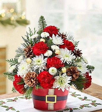 Fill friends and loved ones with the holiday spirit by sending a bunch of bright and merry blooms! Our clean, crisp arrangement of long-lasting carnations, cushion poms, button poms and more is set in a whimsical red tin sporting a belt just like jolly Old Saint Nick's. Realistic pinecones and shimmering gold balls complete the floral festivity.