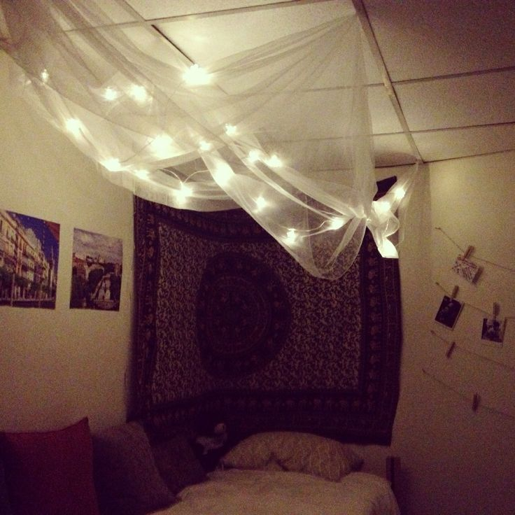 DIY cozy for a dorm room. Canopy made out of sheer curtains from Ikea, flower-string lights from Ikea, tapestry form Urban outfitters for the corner, throw pillows.- erk