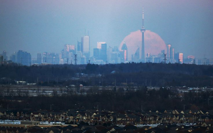 The moon rises over the Toronto city skyline as seen from Milton, Ontario, on January 23, 2016. #  Photos of the Week: 1/23-1/29 - The Atlantic
