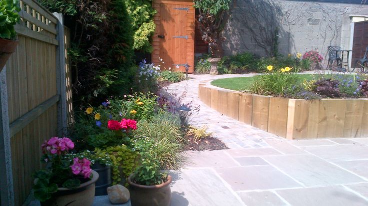 Finished garden with sleeper retaining wall, water feature and sandstone paving.