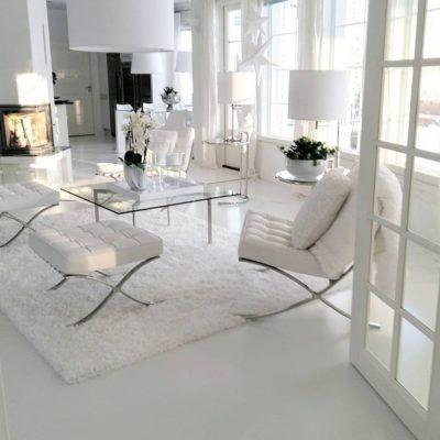 Ylellinen valkoinen ilme olohuoneessa, Barcelona nojatuoli ja rahit sekä kaunis lasipöytä tilan keskellä.