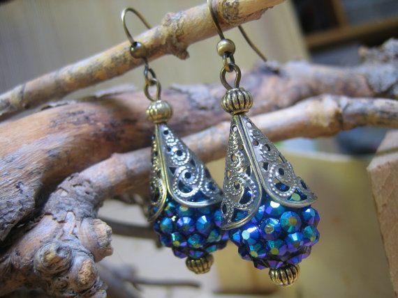 Antiqued brass filigree bead caps and small grooved brass beads embellish these iridescent blue multi-faceted crystal beads. Nickel free brass fish hook ear wires make these lightweight earrings easy to wear, and they come with small stoppers to keep them firmly in place.  $25.00