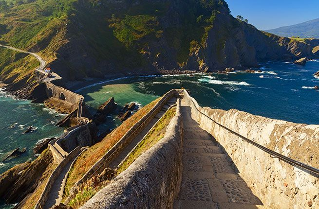 "SAN JUAN DE GATZELUGATXE  ""Castle rock"" in Basque, visitors reach Gaztelugatxe's rocky island outcropping by a stone bridge that looks like a transplanted piece of the Great Wall of China leading to the 10th-century hermitage of St. John the Baptist. The trail to the bridge is a wild footpath that descends through pine forest and ferns."