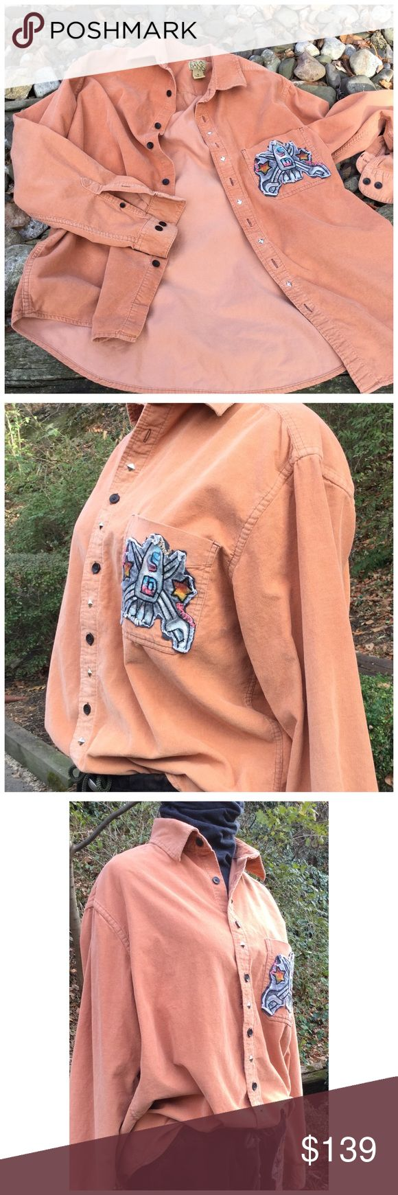 """Rocket (Wo)Man Studded Cord Shirt This is a re-imagined Joseph A Banks men's cord shirt. Bleached, studded with a graffiti rocket appliqué. Men's size M but its shrunk so will fit a woman's M or oversized small. Approx 21"""" pit to pit, 26"""" - 30"""" long at longest point. 18"""" shoulder. Soft, peachy color. Measurements to come. Pants available in closet too DezChic Tops Button Down Shirts"""