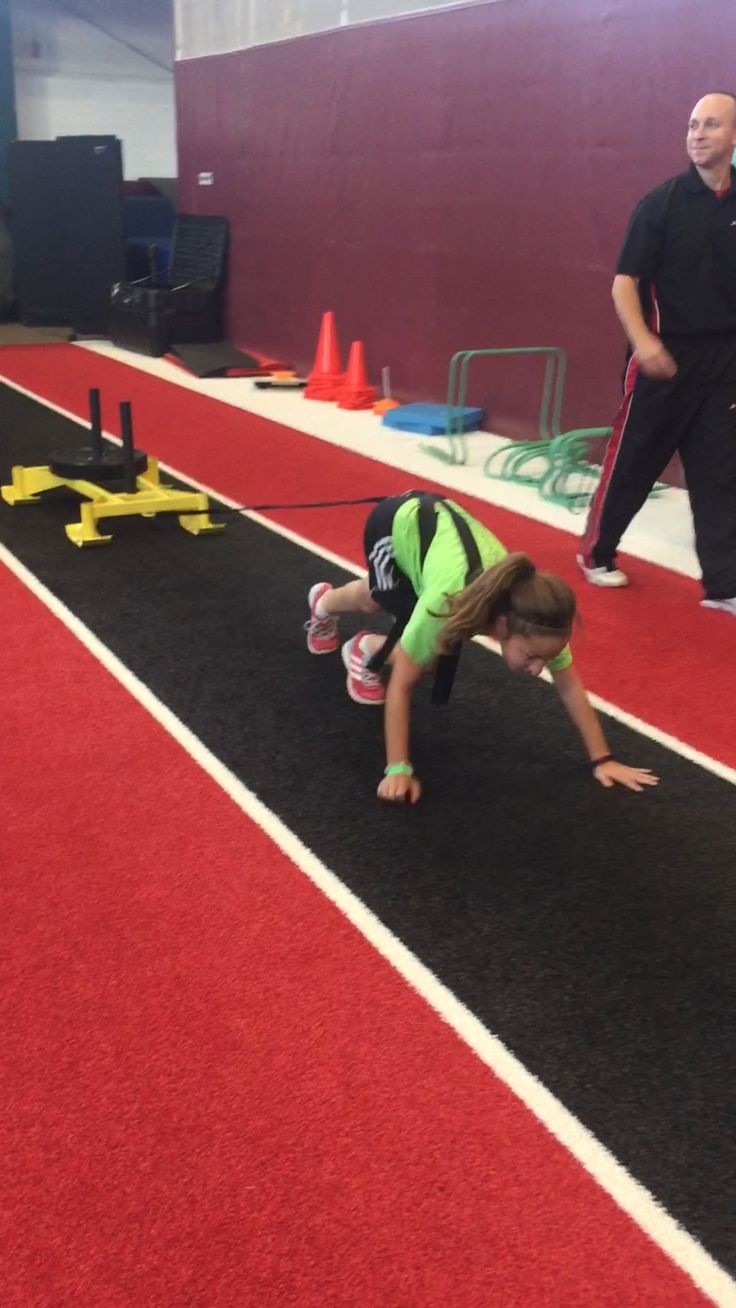Our Jump Start athlete, Megan is performing a resisted bear crawl. Think of a bear crawl as a moving plank. The #athlete must stabilize with their #core to keep this position while moving forward. This is a great exercise to build core #strength.   #Parisi #Speed #School at #HealthQuest  Speed and Strength #Training for #Sports  #Flemington #NJ