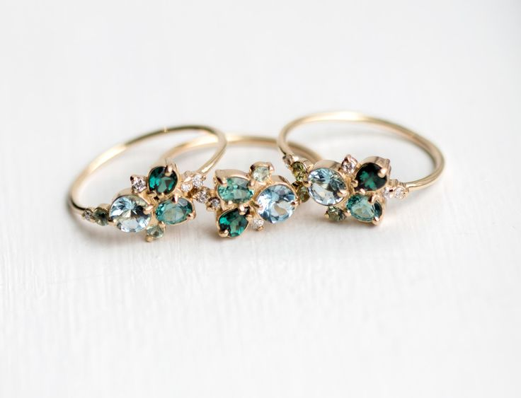 Handmade stacking ring with clustered aquamarine, tourmaline, garnet, sapphire & diamonds in 14k gold prong setting. Shop our ring collection at Melanie Casey.
