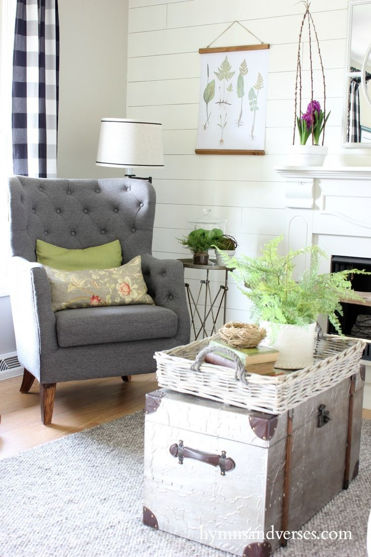 Gray Tufted Chair, ship lap wall, steamer trunk with basket and plant