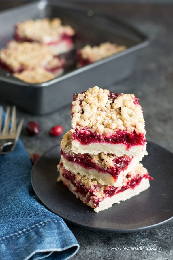 A stack of gluten free cranberry shortbread bars on a black plate. A baking pan has more bars in the background