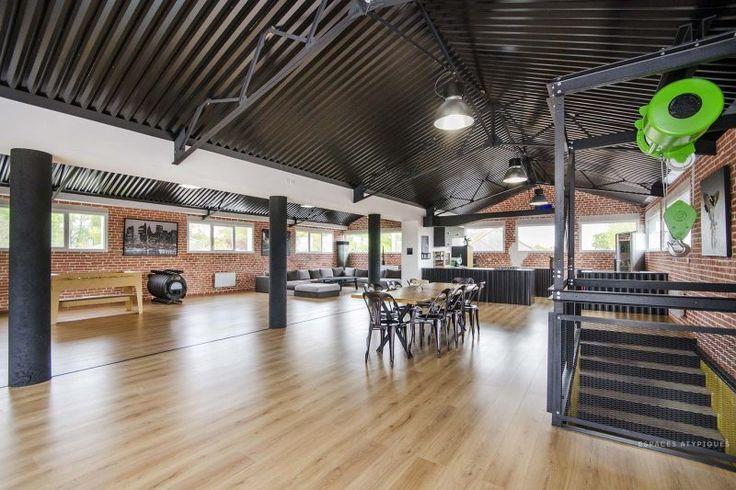 Loft industriel avec plafond en tôle ondulée noire.