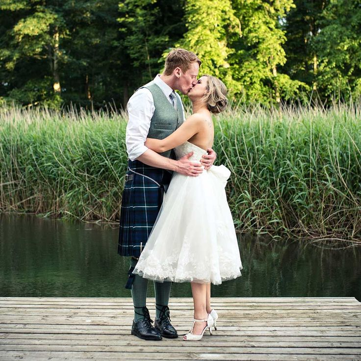 The kilt which this groom is wearing is so handsome and the colours are soft and work perfectly with his bride's tea-length wedding dress. The combination of grey, navy and white looks amazing with the backdrop of this picture and we are getting serious relationship goals from these two.