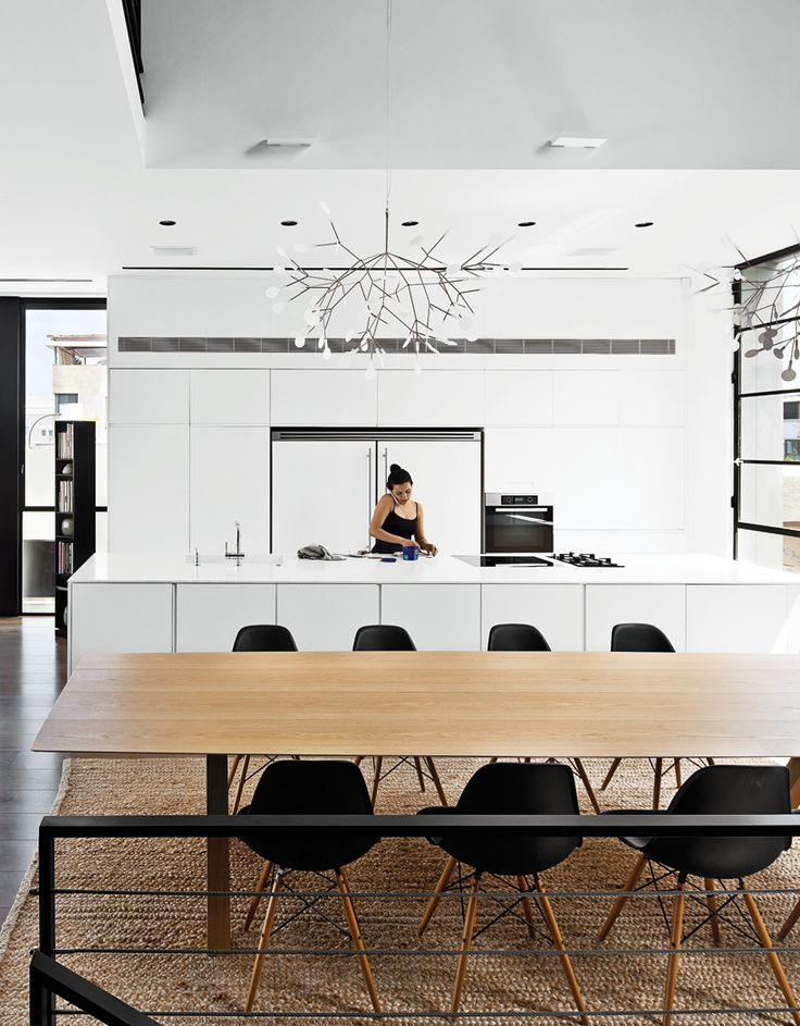 Dining room in Tel Aviv - via Coco Lapine Design similar white kitchen and table, natural rug under it
