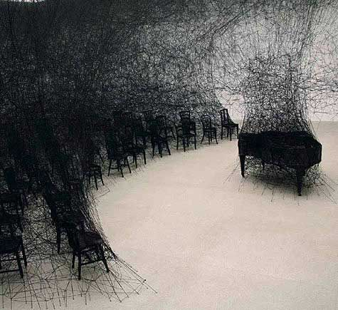 'in silence' (2009) by Japanese installation artist Chiharu Shiota (b 1972). The 'state of being' show at the Centrepasquart, Biel Bienne, Switzerland. Piano, chairs, network made of black wool threads. via design boom- In style by Manfredi Lifestyle. Visit www.manfredilifestyle.com and subscribe for insider's hidden style treasures