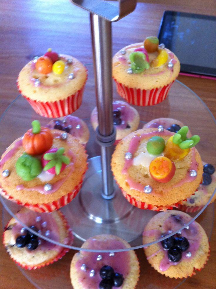Boven Cupcakes met marsepijn, glazuur en eetpareltjes en daaronder cupcakes met eetpareltjes, glazuur en verse bosbessen.