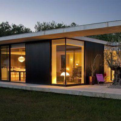 La façade transparente qui fait alterner tôles ondulées en acier et baies coulissantes en aluminium teinté noir.