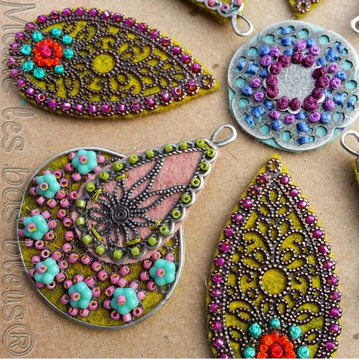 Lovely work combining fabric, felt, metal findings, beads and embroidery...mixed media pendants, focal beads and charms