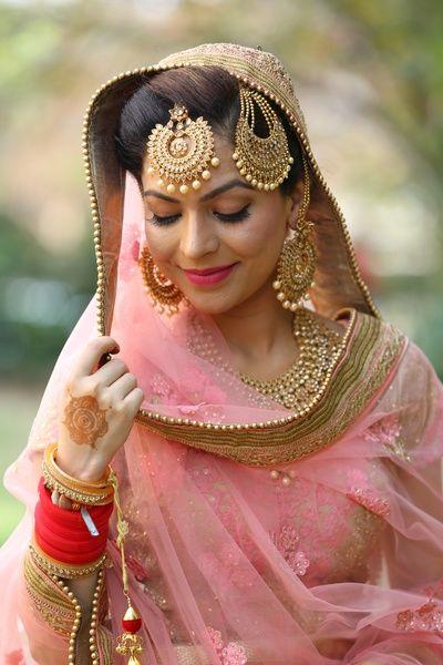 pink bride, pastel pink dupatta, gold border, gold maangtikka, gold jhoomer, gold and pearl earrings