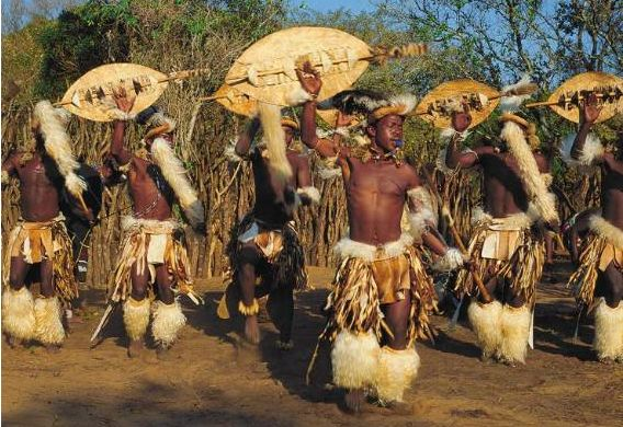 Arts: This picture shows some people doing a traditional dance in South Africa. This dance is called Indlamu. For some dances traditional clothing wear includes traditional head pieces, ceremonial belts, shields, and spears. They use upbeat music and moves to joy happiness and joy through the dance.