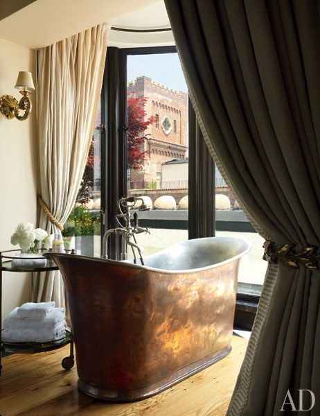 In the master bedroom, an antique copper tub with Waterworks fittings is accompanied by a '50s Baguès trolley | archdigest.com